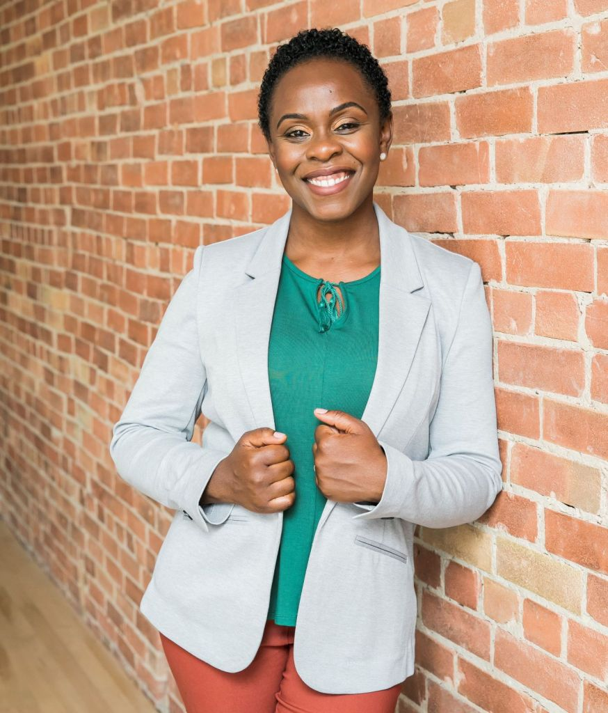 Emily Mills - founder of How She Hustles and Startup & Slay - wearing a grey blazer, green shirt and orange pants in front of a brick wall smiling at the camera