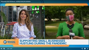 Emily Mills being interviewed on Breakfast Television about Startup & Slay by How She Hustles. Split screen with one woman (Dina) and other screen with Emily wearing a COVID-19 mask with a CityTV microphone. Text on screen reads: Supporting small businesses hustling during the pandemic.